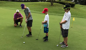 Photo of Dana Saad, PGA Golf Instructor, teaching a lesson to 3 junior golfers